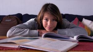 ung ligger på golvet med sina läroböcker