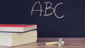 Böcker och kritor framför en svart tavla med texten abc.