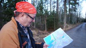 Skogsföretagaren Pekka Riekko tittar på en karta.