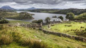 Landskapsbild i Skottland: gröna kullar, grått stenhus och sjön Loch Inchard med bergen Arkle och Ben Stack i bakrunden, Sutherland, Skottlands högländer.