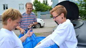 två kvinnor och en man återvinner papper