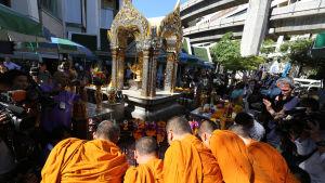 Buddhistmunkar håller en ceremoni vid helgedomen Erawan för en man som förlorade fyra av sina familjemedlemmar i bombdådet.