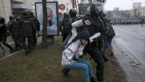 En polis griper en demonstrant i Minsk.