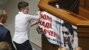 """Savtjenko river ner banderollen """"Frige Savtjenko"""" från parlamentets podie i Kiev 31.5.2016"""
