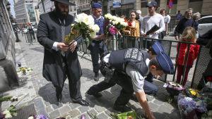 Blommor läggs vid judiska museet i Bryssel där tre personer sköts ihjäl den 24 maj 2014.