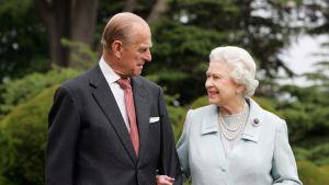 Prins Philip, hertig av Edinburgh, och drottning Elizabeth II av Storbritannien ser på varandra leende medan de står arm i arm.
