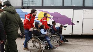 Frivilliga från den syriska Röda halvmånen hjälper skadade rebeller och deras barn att ta sig till väntande bussar