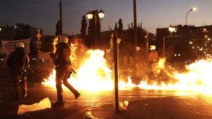 Grekiska poliser försöker undvika molotovcocktails som slängs mot dem i Aten under demonstrationen.