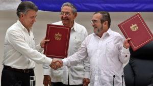 Colombias president Juan Manuel Santos och Farcledaren Timoleón Jiménez skakar hand framför Kubas president Raul Castro.