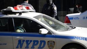 Arkivbild. Polisbil och poliser i New York.