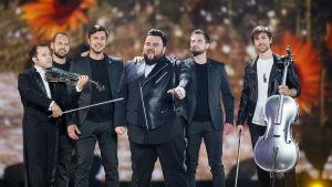 Sex män i svarta kläder på eurovisionsscenen