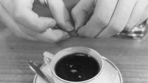 Mies murentaa hashispalasia kahvikuppiin kahvin sekaan.