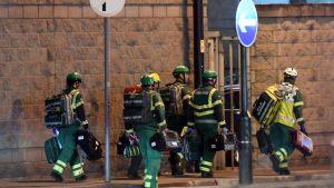 Räddningsmanskap går med utrustning i Manchester.