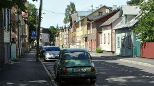 Färggranna trähusfasader på gata i Tallinn.