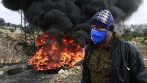 En palestinsk demonstrant passerar en brinnande barrikad utanför en israelisk bosättning nära staden Nablus på Västbanken.