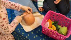 Barn leker med docka på dagis