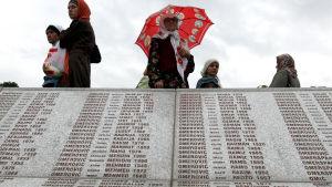Besökare läser namnen på offren av Srebrenicamassakern från ett minnesmärke vid begravningsplasten där en del av offren är begravda. Arkivbild från 11 juli 2009.