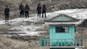 Bild tagen den 7 mars 2016 från den kinesiska staden Dangdong, som gränsar till Nordkorea. På bilden går nordkoreaner förbi en vakt.
