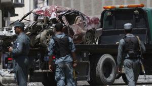 Afghansk polis flyttar en skadad bil från platsen där självmordsbomben detonerade nära Kabuls flygplats.