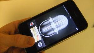 Käsi pitää älypuhelinta, jossa sanelin-sovellus auki.