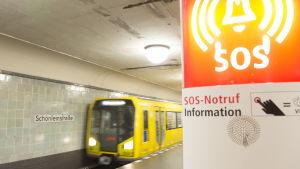 Tåget anländer till plattformen på Schönleinstrasse, i förgrunden en telefon för nödsamtal.
