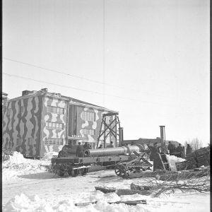 19.3.1940 Russarö. 9 tuuman tykin putkea nostetaan siirtovaunuun, takana kasarmi.