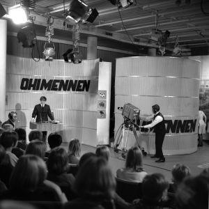 """Tv-ohjelman tekeminen. """"Ohimennen""""-ohjelman kuvaukset tv-studiossa. Juontaja Markku Veijalainen puhuu yleisölle"""