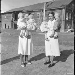 Lastenkoti, jossa hoidetaan toipilaita Aunuksen lastensairaalasta. Tuki: Rajaseudun ystävät: Lastenkodin hoitajia hoidokkeja sylissään.