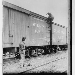 Junapummi kiipeämässä tavarajunan katolle vuonna 1900