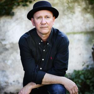 Musikern Micke Allén i svart klädsel och ser in i kameran.