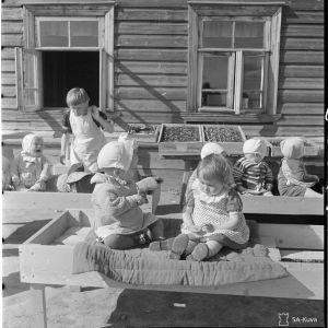 Lastenkoti, jossa hoidetaan toipilaita Aunuksen lastensairaalasta. Tuki: Rajaseudun ystävät: Lapset talon edustalla istumassa. Ikä n. 1,5-3 v.