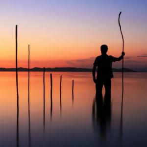 En man står i vattnet. Lång käpp i handen. Långa pinnar i rak rad i vattnet. Solnedgång.