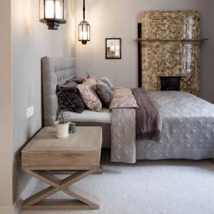 Ett sovrum med en beige kakelugn i bakgrunden.