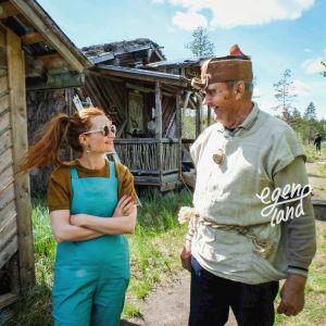 Erkki Kalliomäki päällään kyläpäällikön asu, tuohesta tehty päähine, puinen kaulakoru, pellavainen paita ja toimittaja Hannamari Hoikkala. Taustalla suomaisema, kuvattu Nummijärven Kammi-kylässä.