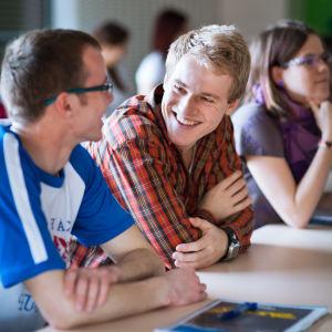 Två män sitter bredvid varandra vid ett bord och ser glada ut.