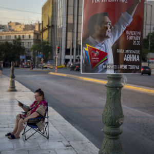 Valaffisch med vänsterpartiet Syrizas ledare Alexis Tsipras. I bakgrunden sitter en äldre dam till synes likgiltig på en stol.