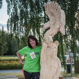 Nainen vihreässä t-paidassa poseeraa puuveistoksen vieressä, veistos esittää karhua, kalaa ja kotkaa