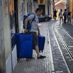 Turist bär på två tunga väskor på en gata i Lissabons historiska centrum.