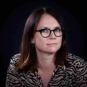 Tummahiuksinen, sinisilmäinen nainen, jolla mustasankaiset silmälasit.