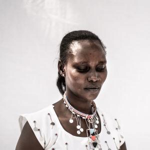 En kvinna står framför en vit vägg.