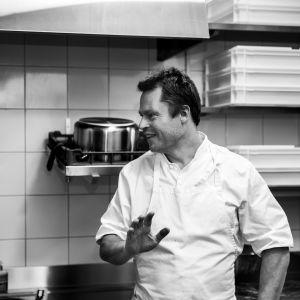 Svartvit bild av Nick Victorzon i köket.