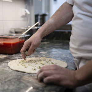 Närbild på kockens händer som breder ut mögelost på en pizza.