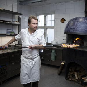 Nick Victorzon skyfflar in en pizza i ugnen.