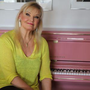 Karita Mattila istuu vaaleanpunaisen pianon edessä