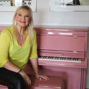 Karita Mattila sitter vid ett ljusrött piano.