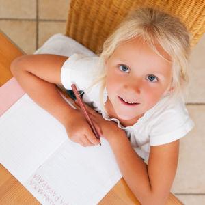 en flicka skriver bokstäver i ett häfte