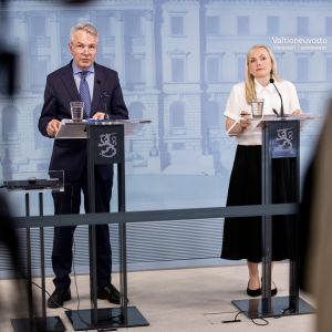 Ministrarna Ohisalo och Haavisto i Statsrådets presskonferens, bakom talarstolar med statslejonet som dekoration