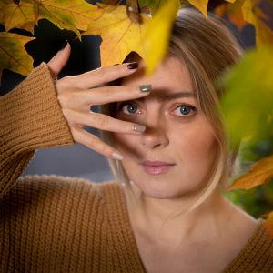 Jenni Rotonen katsoo sormien läpi.