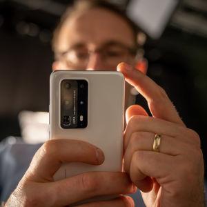 En man håller upp en mobiltelefon framför sig så att baksidan med kameran syns.
