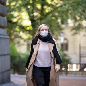 Inrikesminister Maria Ohisalo på väg på en presskonferens. Hon har munskydd på sig och ytterjacka.